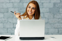 Relaxed businesswoman at her workplace in office Stock Images