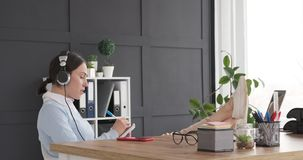 Businesswoman listening music and writing to do list in diary stock footage