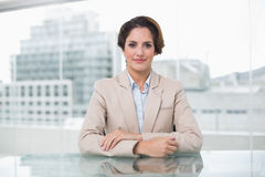 Relaxed businesswoman looking at camera at her desk Stock Photos