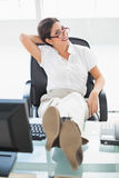 Relaxed businesswoman sitting at her desk with her feet up smiling at camera Royalty Free Stock Photo