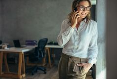 Relaxed businesswoman talking on cell phone stock photo