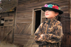 Relaxed in Camo. A cute little girl wearing a camo coat and a fancy flower hat relaxing in front of a deteriorating building. Shallow depth of field. Copy space royalty free stock images