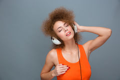 Relaxed carefree curly woman in earphones listening to music Royalty Free Stock Photography