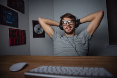 Relaxed carefree man sitting and listening to music from computer Stock Photo