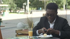 Relaxed carefree young afro american man in stylish eyewear sitting alone at cafe table, using smart phone, reading text. Message with joyful smile during lunch stock video