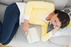 Relaxed casual brunette in yellow cardigan reading a book Royalty Free Stock Photography