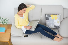 Relaxed casual brunette in yellow cardigan typing on a laptop Royalty Free Stock Photography