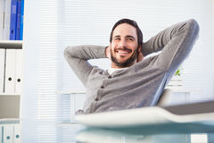 Relaxed casual businessman leaning back at his desk Stock Images
