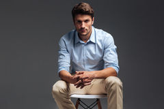 Relaxed casual handsome man in blue shirt sitting on chair Stock Image
