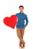 Relaxed casual man holding big red heart. Standing with hand in pocket on white background Stock Photo