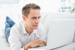 Relaxed casual man using laptop while lying on sofa Stock Image