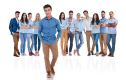 Relaxed casual team leader standing in front of his group. With hands in pockets on white background. They are wearing blue shirts and jeans royalty free stock photo