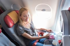 Casual woman flying on commercial passengers airplane, filling in immigration form. Royalty Free Stock Photography