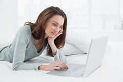 Relaxed casual woman using laptop in bed Stock Photos