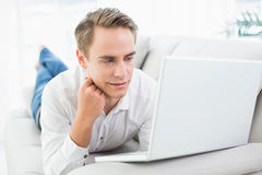 Relaxed casual young man with laptop lying on sofa Stock Photos
