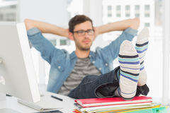 Relaxed casual young man with legs on desk stock photos