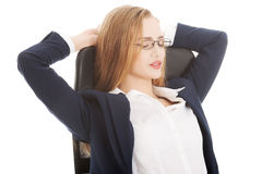 Relaxed caucasian beautiful business woman sitting on a chair. Royalty Free Stock Image