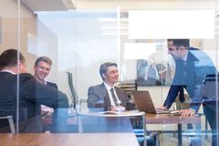 Relaxed cheerful business people sitting and talking at corporate meeting. royalty free stock images