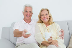 Relaxed cheerful senior couple watching television Royalty Free Stock Images