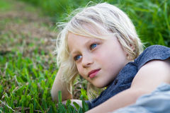Relaxed child outdoors lying on grass. Cute, happy child lying outdoors on grass relaxing royalty free stock photo