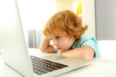 Relaxed child sitting with computer Stock Image