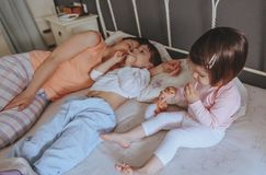 Relaxed children eating cookies over the bed Royalty Free Stock Images