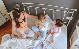 Relaxed children having breakfast over the bed Stock Photos