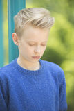 Relaxed concentrated teenager boy outdoor. Portrait thoughtful and daydreaming young blond teenage boy outdoor with closed eyes, concentrated and meditating Stock Images