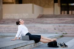 Relaxed content business woman urban lifestyle. Relaxed content urban business woman outdoor working lifestyle Stock Photo