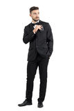 Relaxed cool handsome man in tuxedo with bow tie putting mobile phone in pocket looking away. Full body length portrait isolated over white studio background Royalty Free Stock Image
