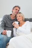 Relaxed couple with coffee cups in living room Royalty Free Stock Photography