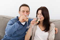 Relaxed couple drinking champagne on the sofa Royalty Free Stock Photos