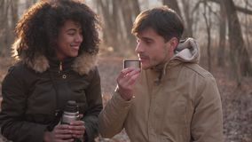 Relaxed couple drinking tea from thermos stock footage