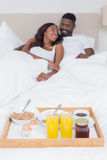Relaxed couple having breakfast in bed together Royalty Free Stock Image