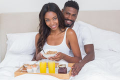 Relaxed couple having breakfast in bed together Stock Photos