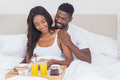 Relaxed couple having breakfast in bed together Stock Image