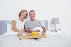 Relaxed couple having breakfast in bed together Royalty Free Stock Photography