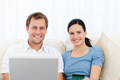Relaxed couple with laptop and credit card. Sitting on the sofa at home Stock Photo