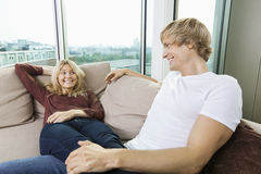 Relaxed couple looking at each other on sofa at home Royalty Free Stock Image