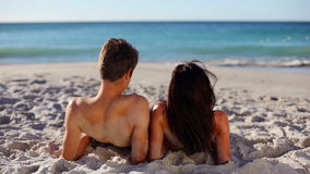 Relaxed couple lying on sand Stock Photography