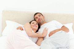 Relaxed couple lying together on their bed Stock Image