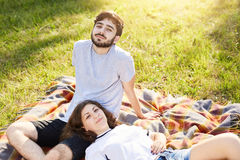 Relaxed couple lying on wrap outdoors having picnic together enjoying good weather. Cute young female lying on her boyfriend`s leg royalty free stock photo
