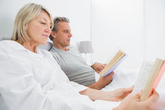 Relaxed couple reading books in bed Royalty Free Stock Image