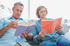 Relaxed couple reading books on the couch Royalty Free Stock Image