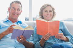 Relaxed couple reading books on the couch smiling at camera Royalty Free Stock Photo