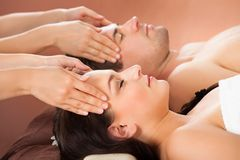 Relaxed couple receiving head massage at spa. Side view of relaxed young couple receiving head massage at spa Royalty Free Stock Photos