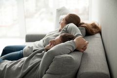 Relaxed couple resting or having nap leaning on comfortable sofa. Relaxed couple asleep resting or having nap sitting on comfortable sofa enjoying daytime doze royalty free stock image