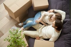 Relaxed couple resting on sofa on moving day, top view royalty free stock photos
