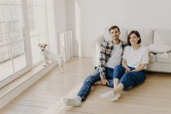Free Relaxed Couple Sit On Floor Near Couch, Embrace And Smile, Dressed In Casual Clothes And White Socks, Enjoy Domestic Atmosphere, Royalty Free Stock Photos - 160015168