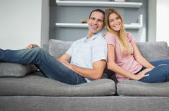 Relaxed couple sitting back to back on the couch together Royalty Free Stock Photo